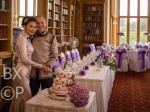 Chim & Kevin cutting their cake in the Library of Stoke Rochford Hall